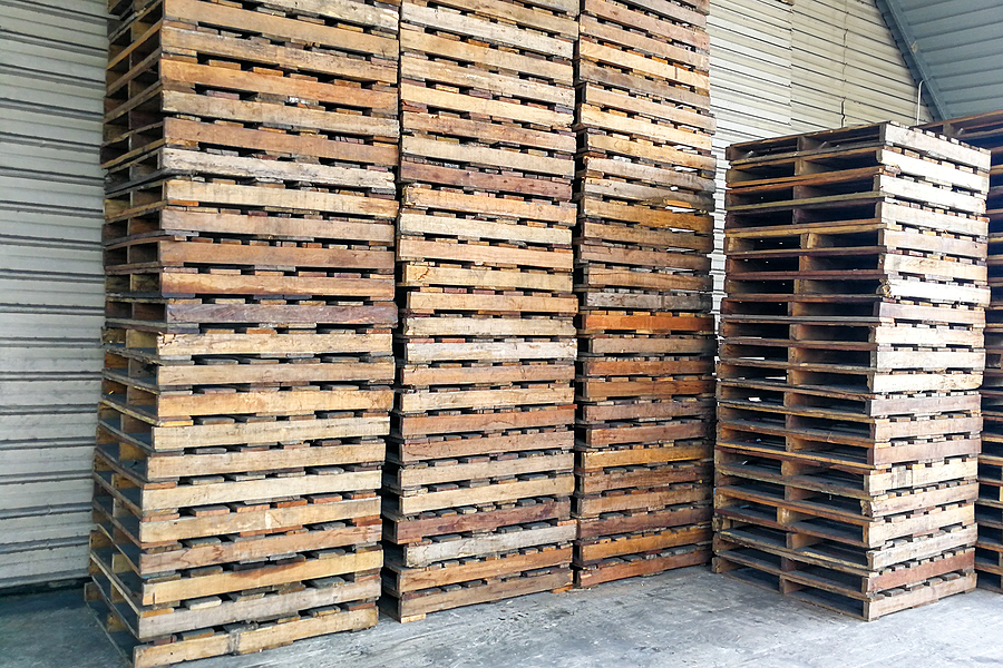 stack of wooden pallets at warehouse. pallets are used extensively in goods merchandise transportation logistic industry.