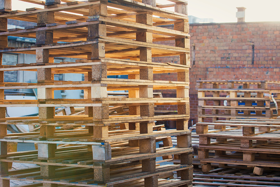 outdoors background of warehouse wooden shipping pallets stacked on top of one another for industrial transportation at recycling depot. piles of euro type cargo pallets.