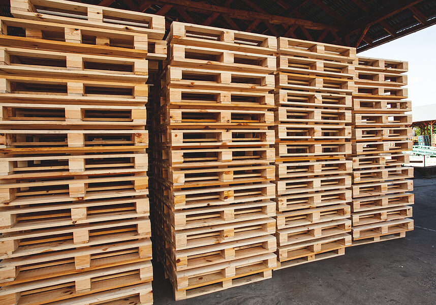 multiple stacks of wooden pallets in the stock